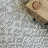 Recycled plastic bottle grey rug with geometric pattern.  Also visible is the corner of a reclaimed wood coffee table.