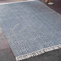 Navy blue kilim rug 120 x 180cm with geometric pattern. White fringe at both ends. Beside a bottle of wine and glass. Made from environmentally friendly recycled plastic bottles.