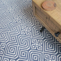 Navy blue kilim rug made from recycled plastic bottles with geometric pattern.  On top is a reclaimed wood coffee table.