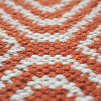 Close up of terracotta red kilim rug with geometric pattern. Made from eco friendly recycled plastic bottles.