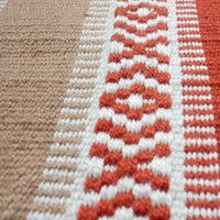 Close up showing detail of red and brown rug, woven from recycled plastic bottles.