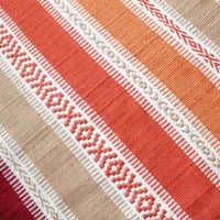 Section of a red, brown and burnt orange striped eco rug, made from recycled plastic bottles and ethically sourced.