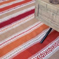 The corner of a coffee table, resting on a striped orange, red and beige recycled plastic bottle striped eco rug.