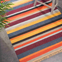 Multi-coloured striped recycled plastic bottle rug. Orange, purple, blue, black. Eco friendly and suitable for indoor or outdoor use.  A plant and stool are in shot.