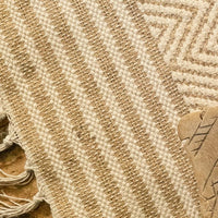 Close up of recycled chenille cotton and jute rug, with patterned sections alternating between stripes and chevrons.  Natural beige colour.