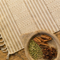 Recycled chenille cotton and jute rug, with patterned sections alternating between stripes and chevrons. Beside it, a small wooden ball containing spices.