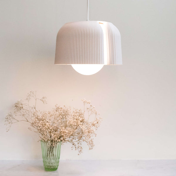 White 3D printed recycled plastic bottle pendant lamp.  An open section down one side allows a chink of light through.