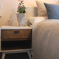 White bedside table containing one drawer and empty space below for books. To the right is a Namaste fair trade recycled plastic bottle taupe throw-blanket with diamond pattern.