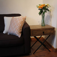 Image showing showing ReChic reclaimed wood side table (with drawer) with vase and orange & white flowers, beside brown sofa with geometric orange and cream textured cushion.