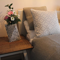 Eco-friendly home decor - a bed is dressed with ReChic recycled grey cushions and plastic bottle knitted throw.  On the end table beside it is a geometric Ecopixel grey, white and black vase with white and pink bouquet of fresh flowers.