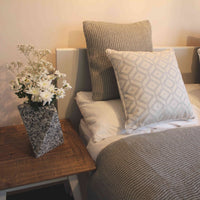 Sustainable home decor.  Bed dressed with recycled knitted grey throw and cushion and geometric grey cushion. Beside is a geometric grey pixelated vase with white flowers.