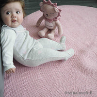 Baby sat on a round, pink recycled cotton rug.  Goodweave certification ensures it is ethical.