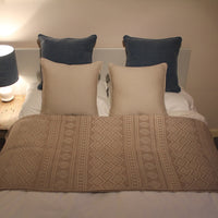 Bed with grey, taupe and navy blue cushions and throws, all made from recycled materials.