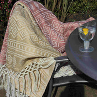 Two recycled plastic bottle (PET) outdoor eco picnic blankets, with geometric design and fringe. One pale red, the other pale yellow.  Displayed on a garden chair.