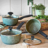Three Prestige Eco Saucepans displayed on a wooden block. The pans are made from recycled aluminum and have a green, speckled coating.
