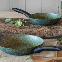 Two Prestige Eco frying pans on a wooden block. They have a dark green colour with white flecks on them.  20 and 24cm