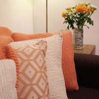 Selection of ReChic eco-friendly home decor.  Recycled sustainable cream and orange recycled cushions. In the background is a recycled glass decorative vase containing fresh orange and white flowers.