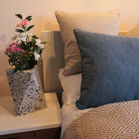 ReChic navy blue and taupe recycled eco-friendly cushions on a bed.  Beside is an Ecopixel recycled geometric plastic sustainable vase with fresh pink and white flowers.