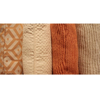 Stacked ReChic recycled cushions of various white, cream and orange shades.  Geometric patterns, textured and knitted.