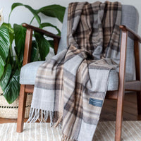 Folded recycled wool throw. Tartan check design of natural colours, grey, beige, brown.  Draped across a chair.
