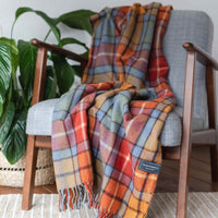 Tartan recycled wool throw or blanket. Check design of red, orange, light blue and green.  Draped across a chair.