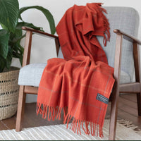 Recycled sustainable wool blanket or throw.  Rusty red with a light check tartan design.  Draped across a chair.