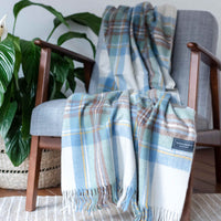 Recycled wool throw or blanket. White base colour, with pastel blue, green and brown check.  Draped across a chair.