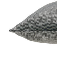 Close up showing piped edge of ReChic recycled cotton and PET cushion with fine chevron design in dark grey and off-white.