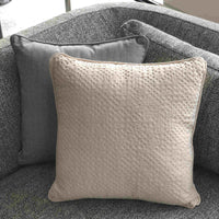 ReChic sustainable recycled cotton and plastic bottle square cream cushion, with a texture like inverted bubble wrap. Positioned on a grey sofa.  Made in the UK.