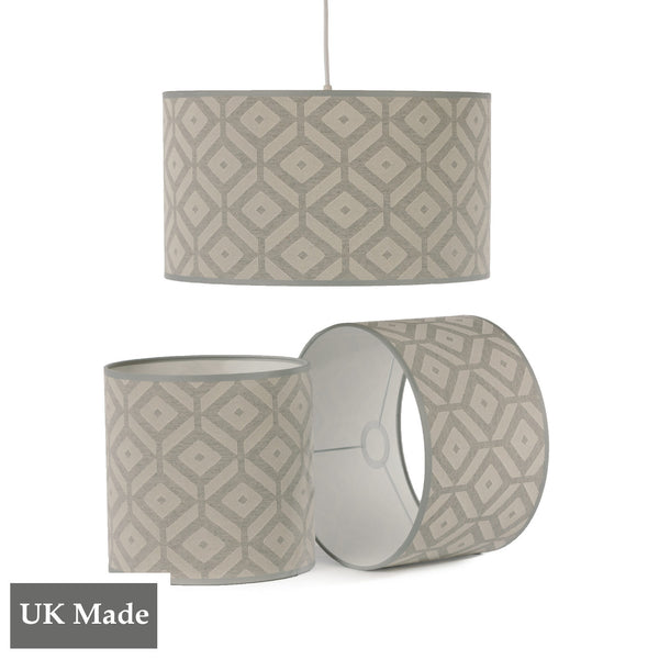 Three ReChic recycled cotton lampshades in light grey and white with geometric, hexagonal design .  One is hanging, two sit below it, including one on its side.