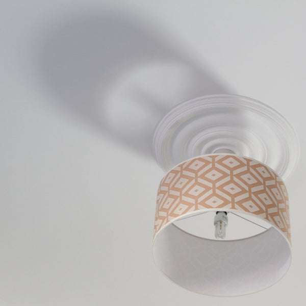 ReChic large recycled cotton cylinder lamp shade with orange and white geometric design. Displayed hanging from the ceiling. 16 x 9 inches.  40cm.