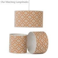 Three ReChic recycled sustainable cotton drum lampshades.  Orange and white geometric tessellating design of diamonds and hexagons.