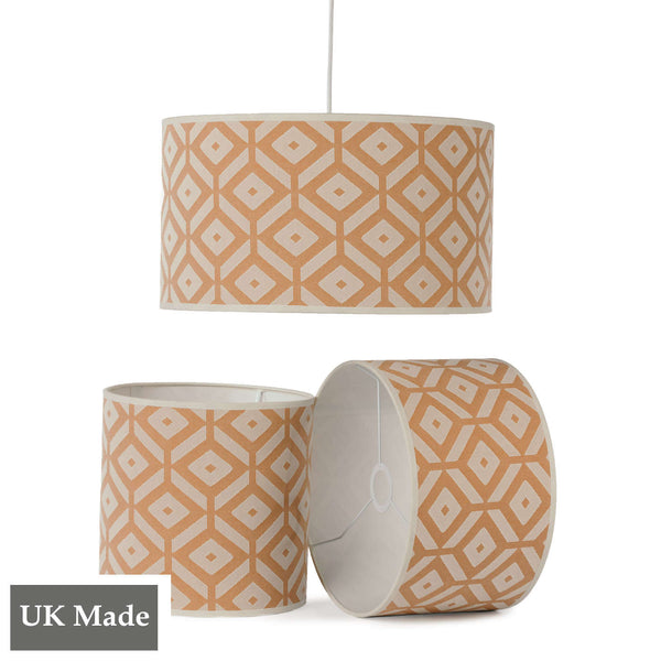 Three ReChic recycled cotton lampshades in orange and white with geometric, hexagonal design .  One is hanging, two sit below it, including one on its side.