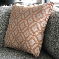 ReChic sustainable, recycled cotton and PET (plastic bottle) cushion with geometric tessellation of orange and off-white hexagons. Presented on the corner of a grey sofa. 45 x 45cm and UK made.