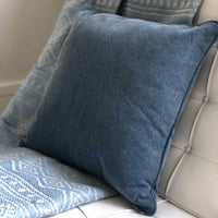 ReChic sustainable, recycled cotton and PET cushion in stonewash navy blue.  Sat on a white chair.  45 x 45cm