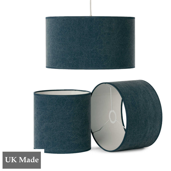 Three ReChic recycled cotton lampshades in stonewash navy blue.  One is hanging, two sit below it, including one on its side.