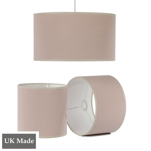 Three ReChic recycled cotton lampshades in stonewash soft pink.  One is hanging, two sit below it, including one on its side.