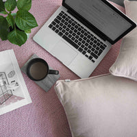 Flat-lay view of recycled pink rug, pink cushions, laptop, coffee mug and small plant.  Eco-friendly home decor.