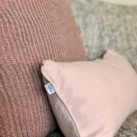 Close up showing piped edge of a soft pink rectangular cushion made by ReChic from recycled cotton.  Beside a mauve pink knitted cushion made from recycled plastic bottles.