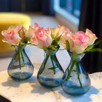 Three small grey recycled glass bud vases, containing white/pink roses.