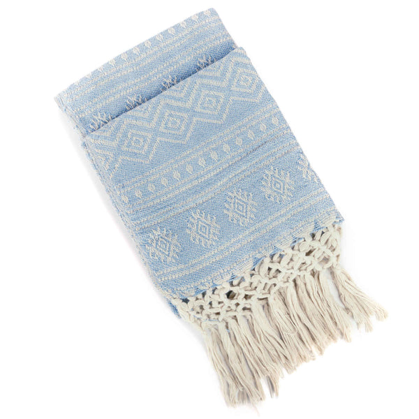 Folded sustainable recycled plastic bottle sky blue eco throw-blanket with off white geometric pattern and knotted fringe.  Machine washable, suitable for indoor or outdoor.