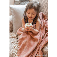 Toddler sat holding a cupcake whilst wrapped in a pale red blanket made from recycled plastic bottles (PET).