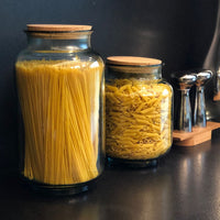 Two clear recycled glass storage jars with cork lids.  The large jar contains spaghetti, the medium sized jar contains penne pasta.