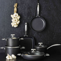 Selection of Scanpan Pro IQ pans on a table. A frying pan and garlic hang against a charcoal grey wall.