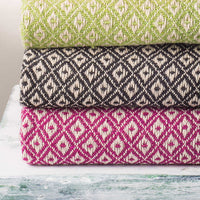 Stack of three recycled cotton blankets with diamond design. From top to bottom they are green, black and purple.