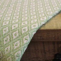 Pale green throw or blanket with white diamond design, made from recycled cotton.  Draped across a wooden table.