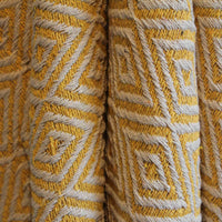 Close up showing detail of recycled cotton yellow throw or blanket.  Eco-friendly and ethically sourced.