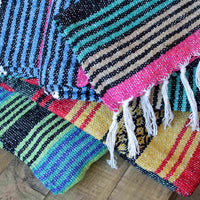 Three folded environmentally friendly recycled cotton striped blankets. The first is predominantly, blue and green, the second a mixture of bright colours, the third is orange, black and red. All have a white fringe.