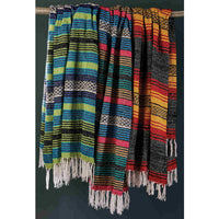 Three recycled cotton striped blankets hanging from a rail. The first is predominantly, blue and green, the second a mixture of bright colours, the third is orange, black and red. All have a white fringe.  Sustainable home decor.