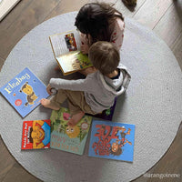 Birds-eye view of two young children reading books on a round recycled grey cotton rug